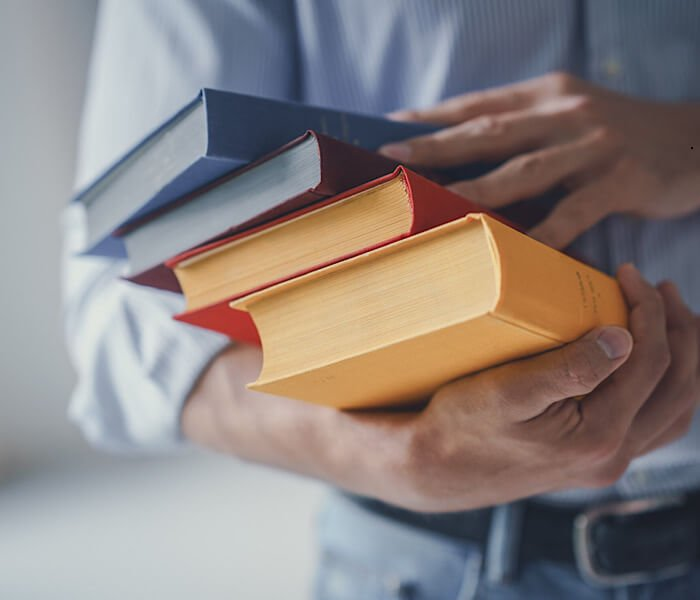 man holding stack of books to read for finding writing prompts for his book idea