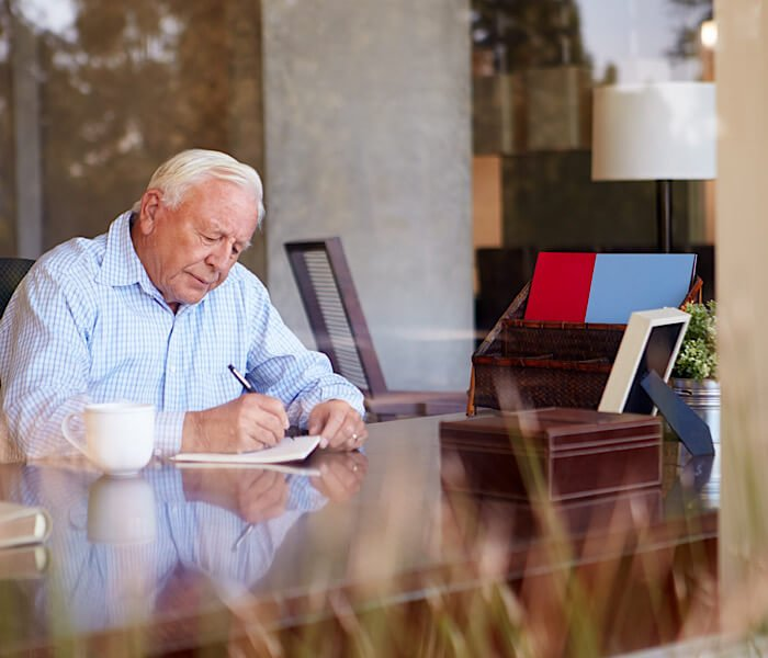 older man writing down his personal anecdotes as writing prompts for his book