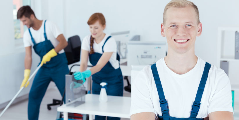man smiling while people clean their office space