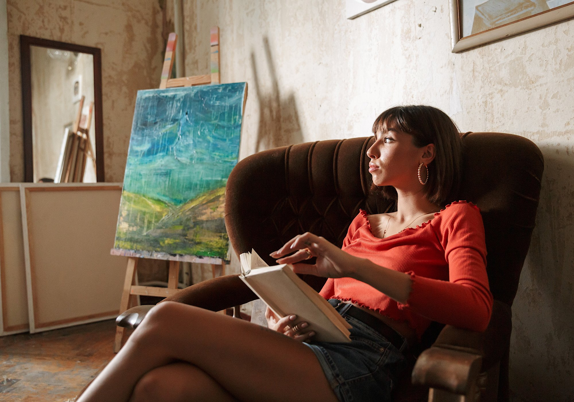 Beautiful young woman artist sitting on armchair in the art studio, relaxing, reading book