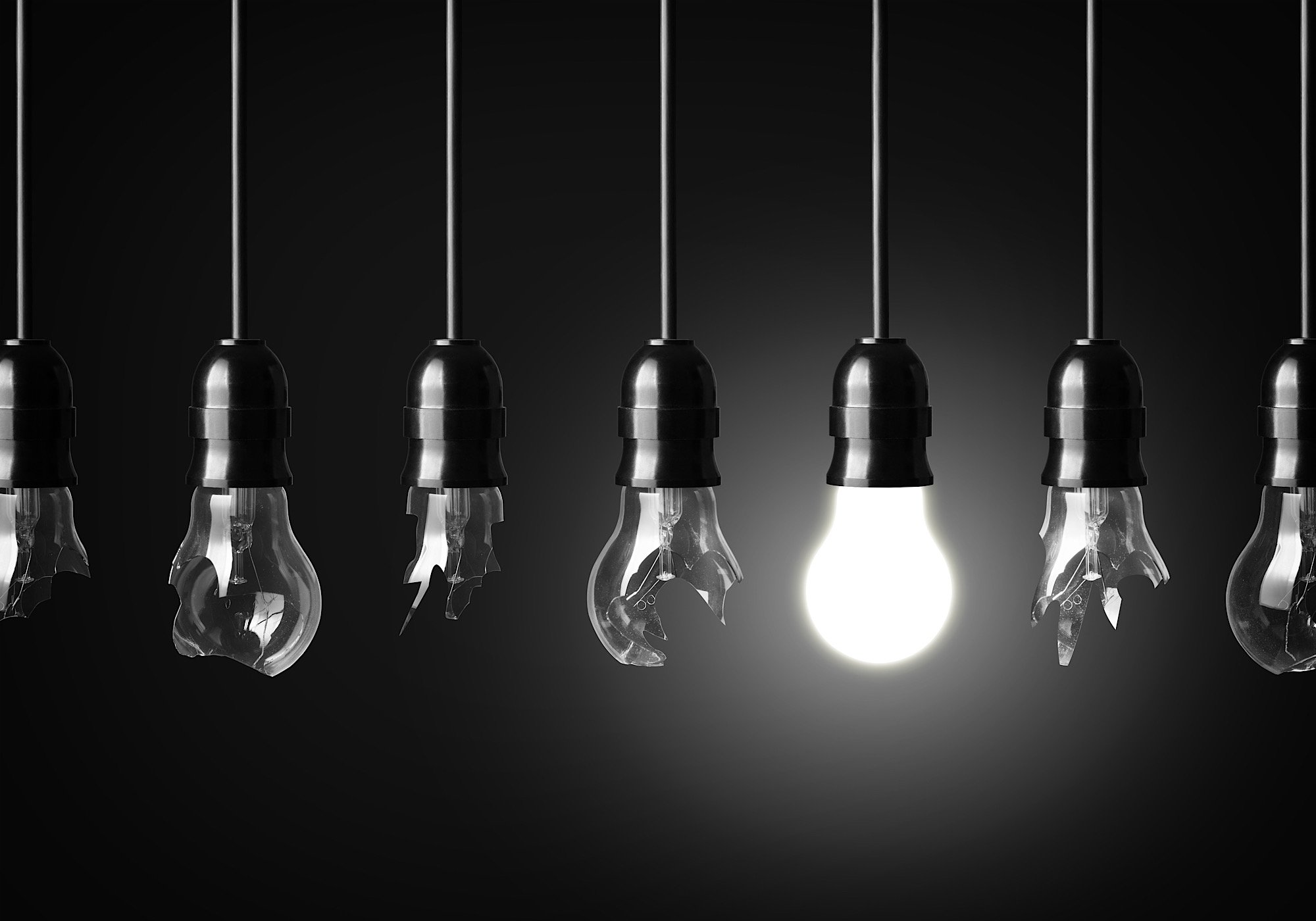 A row of lightbulbs in black and white. Only one of the bulbs is lit