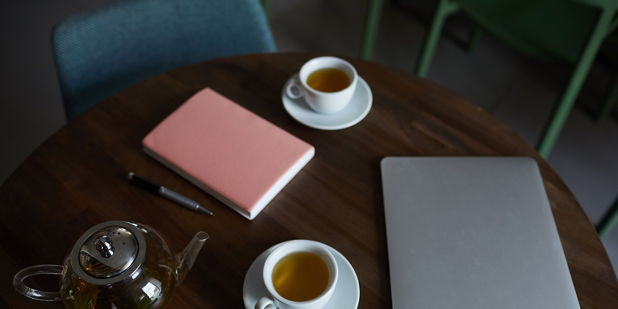View of two white porcelain cups of green herbal tea, notebook with pen, laptop and teapot on round wooden table in cafe